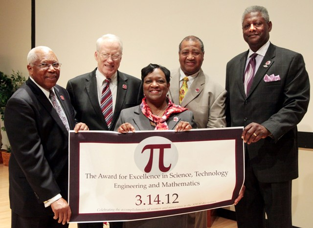 Platform guests display a sign signifying the launching of a new endowment fund in honor of Juliette B. Bell, center.